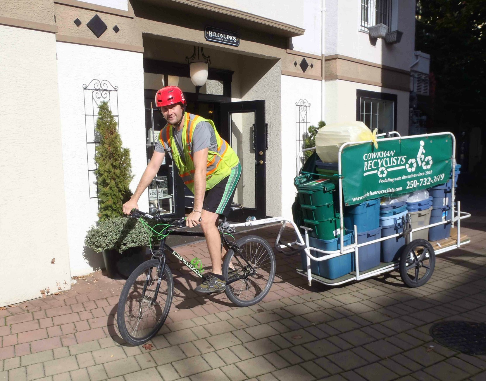 A bicyclist towing a Cowichan Recyclists bike trailer while doing the rounds in downtown Duncan