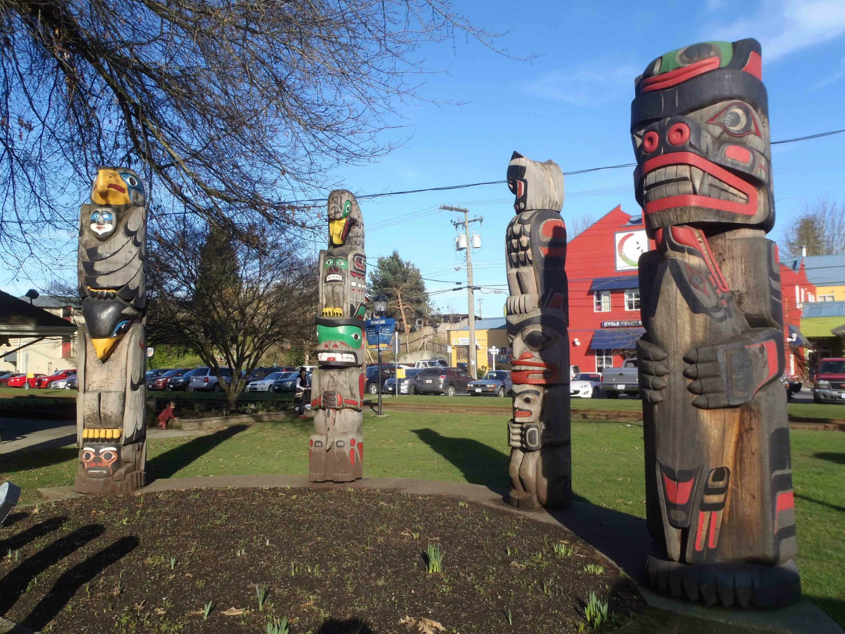 Four totem poles displayed in Charles Hoey Park on Canada Avenue. Left to right: Transformation In Life, The Friendship Pole, Owl Pole and Kwagu'l Bear Holding A Seal