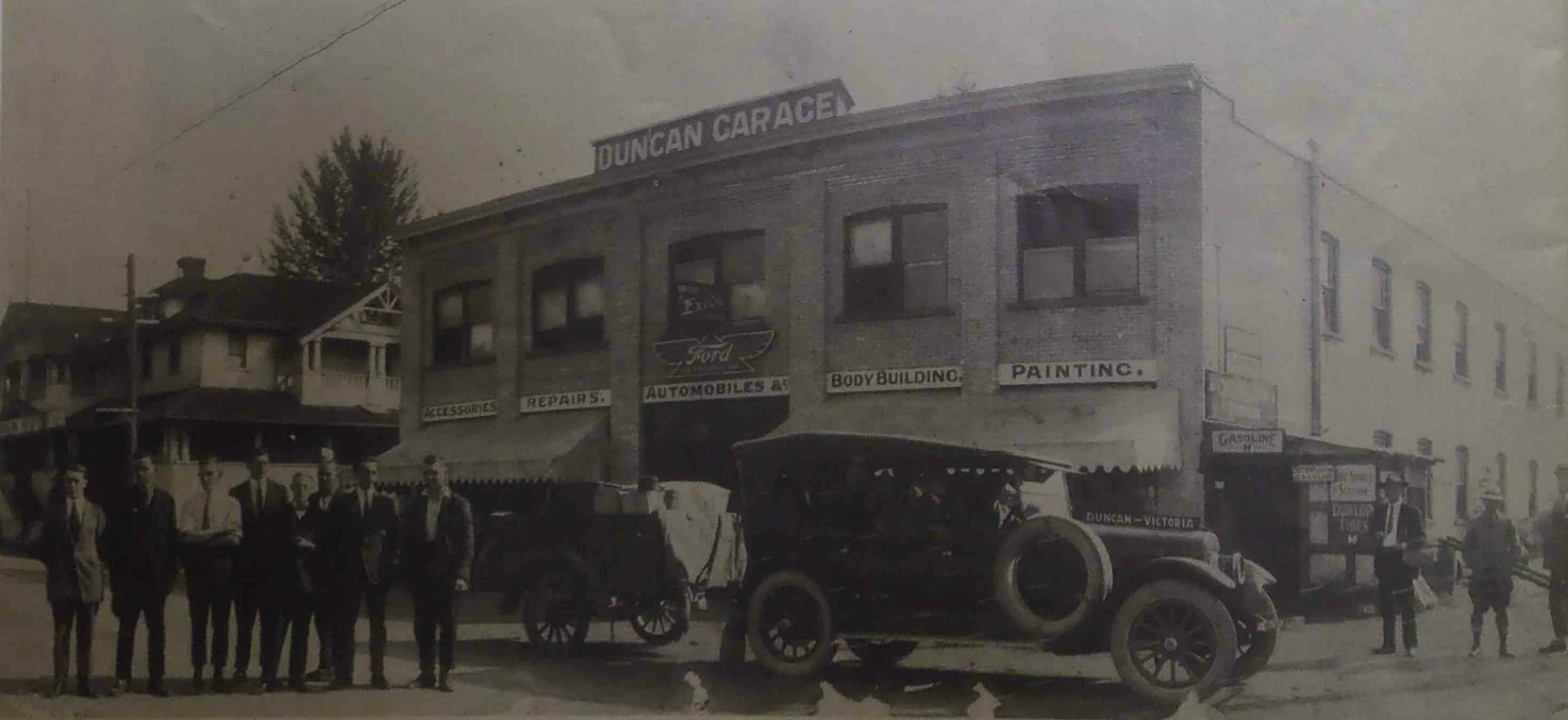 Duncan Garage, circa 1921. The car in the photo is the Duncan to Victoria bus service operated by Duncan Garage. Note the trailer behind the car.
