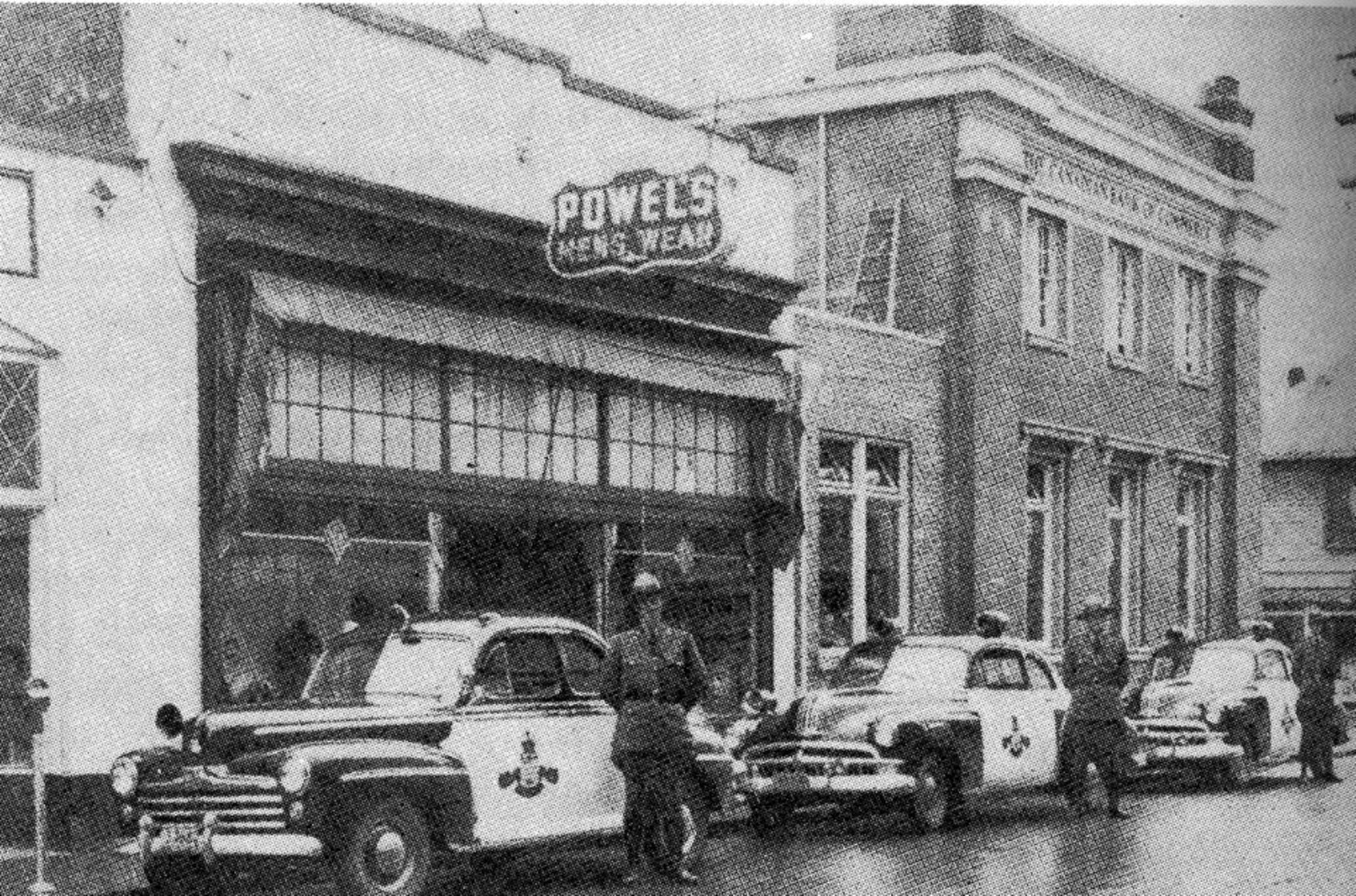 45 Craig Street as Powel's Men's Wear, circa 1950, with B.C. Provincial Police officers in front. The building on the right was the Canadian bank of Commerce, now demolished. The CIBC branch now stands on that site. (Note: we are currently checking for the source of this photo)